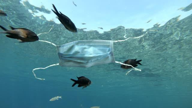 gebrauchte medizinische gesichtsmaske verschmutzende ozean - plastikmaterial stock-videos und b-roll-filmmaterial