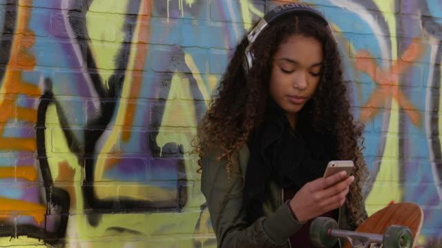 vídeos de stock, filmes e b-roll de utilizando um telefone celular na cidade - andar de skate
