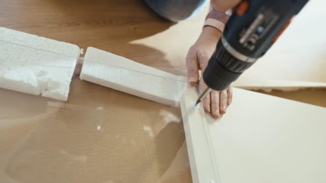 slo mo mit einem akkubohrer zum anziehen von schrauben an den möbeln - möbel stock-videos und b-roll-filmmaterial