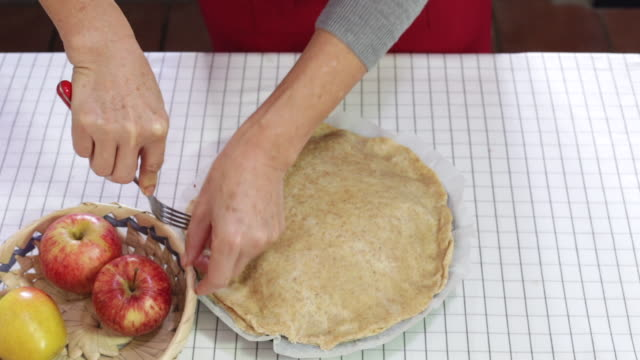 using a fork to crimp the edge of apple pie - pastry dough stock videos & royalty-free footage