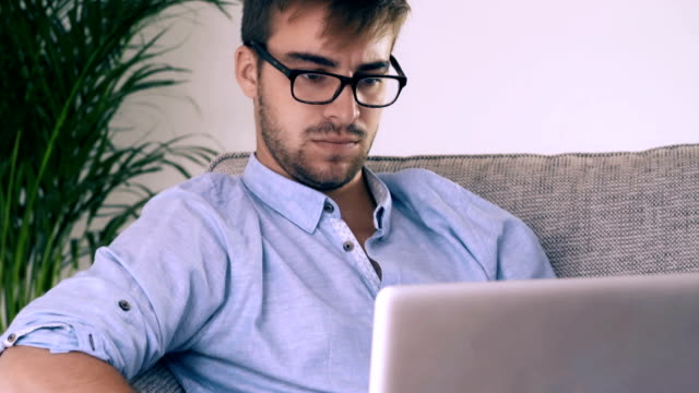 using a laptop and sofa. man with glasses. 1 - teleworking stock videos and b-roll footage