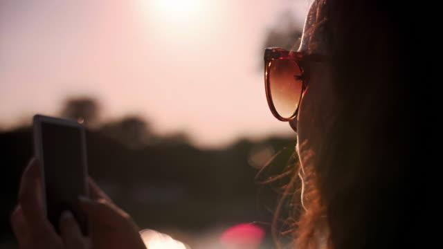 using a mobile phone/ krakow/ poland - sunglasses点の映像素材/bロール
