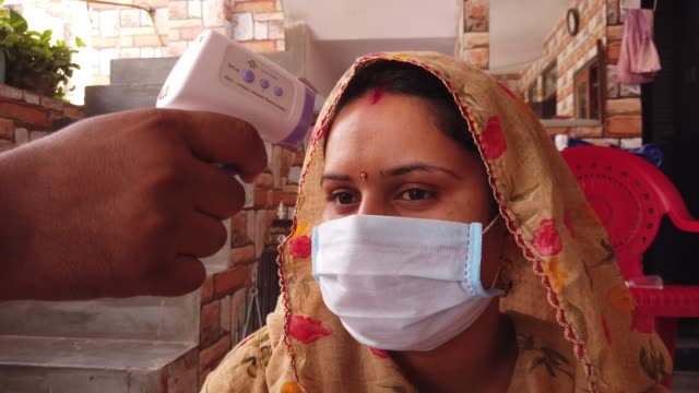 using a non-contact infrared digital thermometer to measure high fever temperature during the lockdown on forehead of a woman at home - infectious disease stock videos & royalty-free footage