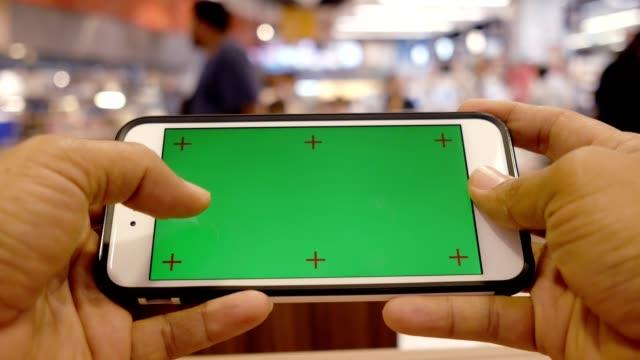 pov: 緑色の画面で携帯電話を使用してください。 - 横位置点の映像素材/bロール