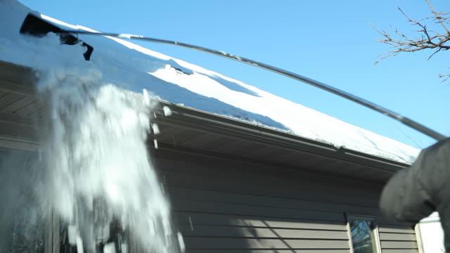 vídeos de stock e filmes b-roll de com um telhado ancinho para a remoção de neve de inverno - ancinho equipamento de jardinagem