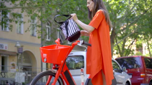 använda en delad elektrisk cykel - endast en ung kvinna bildbanksvideor och videomaterial från bakom kulisserna