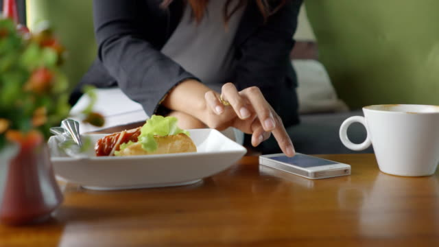 using a smart phone at a table in a cafe
