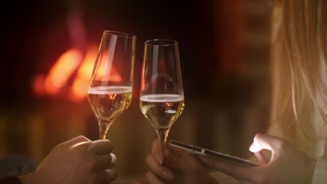 ms using a smart phone while drinking a wine by the fireplace - champagne flute stock videos & royalty-free footage