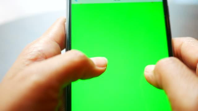 vídeos y material grabado en eventos de stock de uso de un teléfono inteligente con una pantalla verde - asociación norteamericana de telecomunicaciones e internet