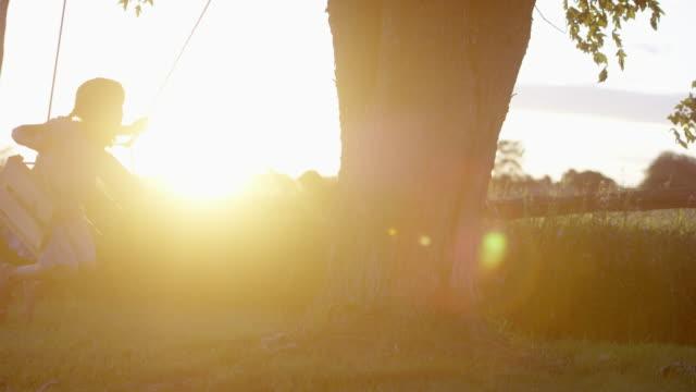 vídeos de stock e filmes b-roll de andar de baloiço ao pôr do sol - cerca