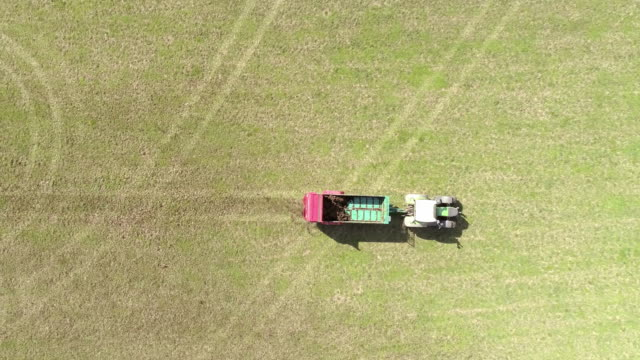 aerial using a tractor for spreading manure over the grass - agricultural machinery stock videos and b-roll footage