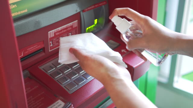 using alcohol based sanitizer spray on automated teller machine button for disinfecting - prevention stock videos & royalty-free footage