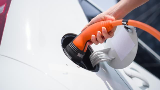 verwendung alternativen energien tanken elektroauto in innenstadt - tankstelle stock-videos und b-roll-filmmaterial