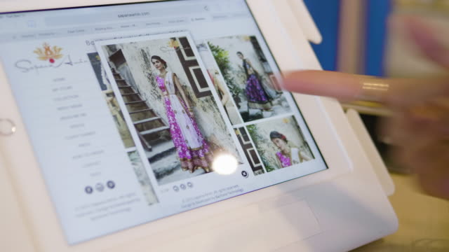 using an tablet, a fashion designer shows her clothing designs to a boutique owner. - online shopping stock-videos und b-roll-filmmaterial
