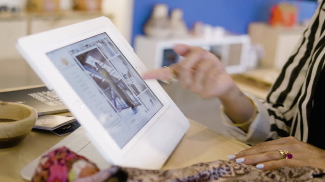using an tablet, a fashion designer shows her clothing designs to a boutique owner. - sälja bildbanksvideor och videomaterial från bakom kulisserna