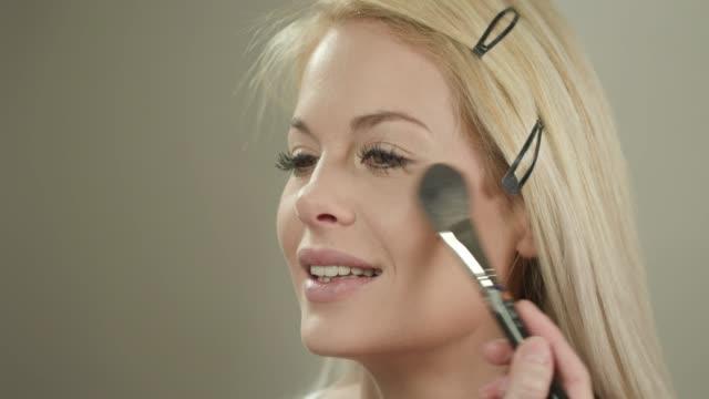 vídeos de stock, filmes e b-roll de usando pincel de blush para até mesmo blush - blush
