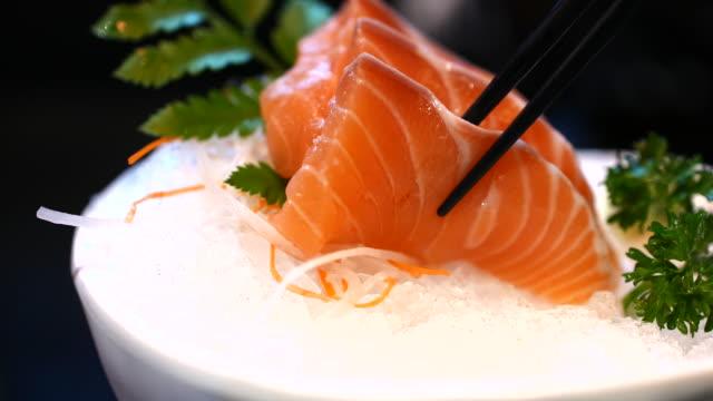 Using Chopstick eating Salmon Sashimi, Japanese Food