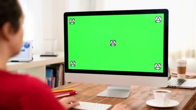 verwenden von chroma-key-desktop-computer im büro - über die schulter stock-videos und b-roll-filmmaterial