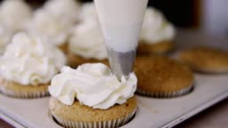 Using cooking bag, confectioner making cupcake. Put butter cream on tasty muffin