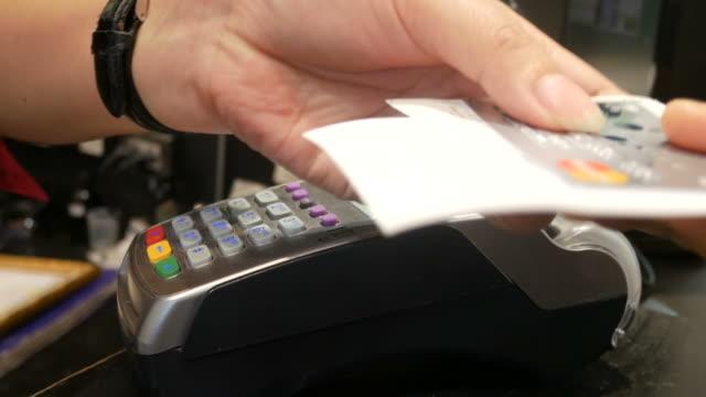 vídeos de stock e filmes b-roll de using credit card - vendedor trabalho no comércio