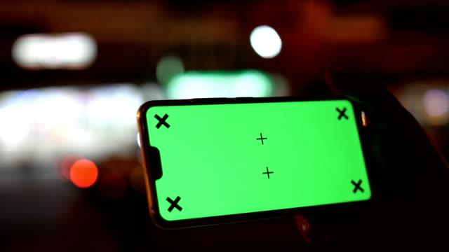 vídeos y material grabado en eventos de stock de utilizando digital smart phone en modo apaisado con una pantalla verde con fondo de semáforo nocturno, chroma key - horizontal