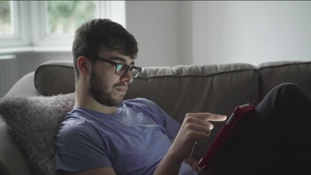 vídeos de stock e filmes b-roll de usando tablet digital, sentado confortavelmente em um sofá. ds - homens jovens