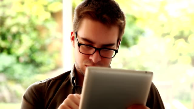 Using digital tablet. Young man wearing glasses.