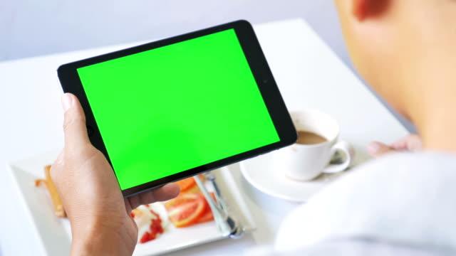 Mit grünen Bildschirm digital tablet mit Frühstück