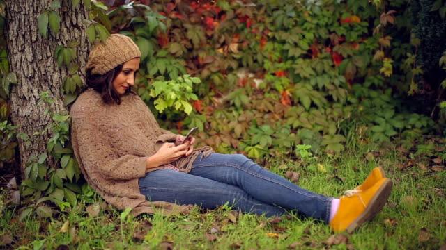 vídeos de stock e filmes b-roll de using her phone in the park on an autumn's day - gorro de lã