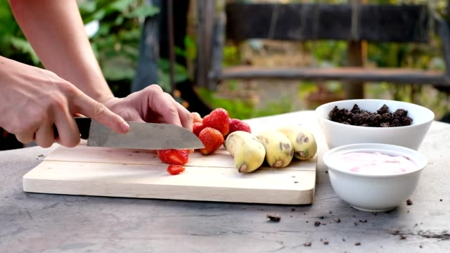 using knife cooking sliced strawberry fruit on chopping block with banana, chocolate and yogurt - table knife stock videos & royalty-free footage