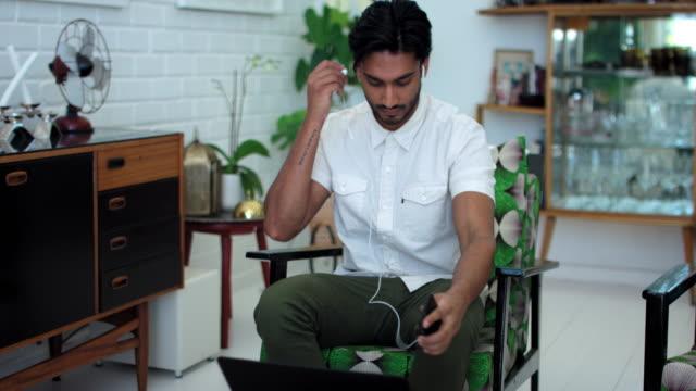 vidéos et rushes de using laptop and phone - seulement des jeunes hommes