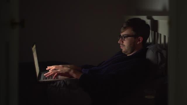 vídeos y material grabado en eventos de stock de usando una computadora portátil en la cama por la noche. 1 - estudio habitación