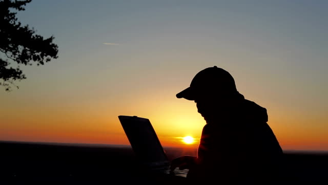stockvideo's en b-roll-footage met using laptop on summit at sunset - baseballpet