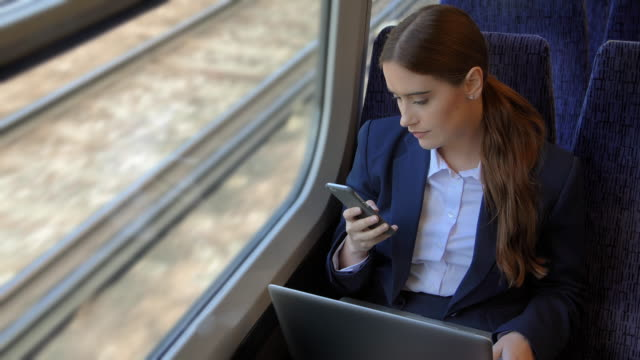 using laptop, reading phone message. business woman on a train. - businesswoman stock videos & royalty-free footage