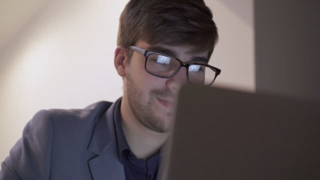 Using laptop, screen reflection in eyeglasses.