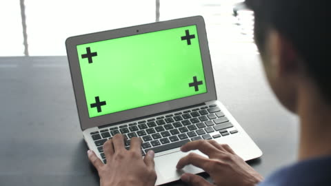 stockvideo's en b-roll-footage met met behulp van laptop met groen scherm - over shoulder