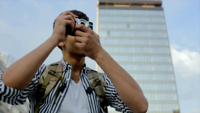 Using old fashionable photographing equipment on travel,young hipster men