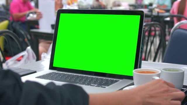 using on laptop with green screen in a restaurant - inquadratura da sopra le spalle video stock e b–roll