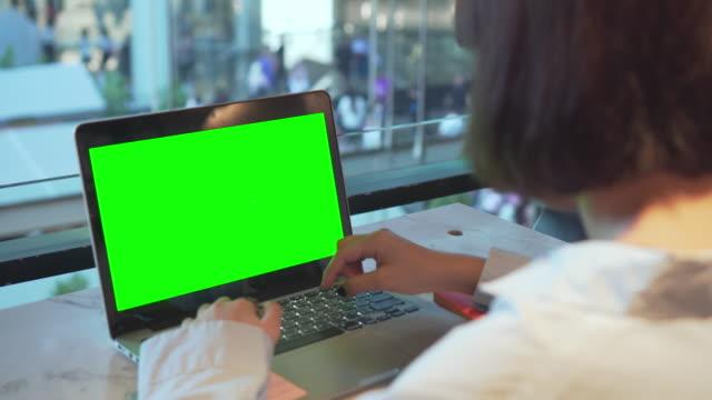 verwendung auf laptop mit green screen in einer shopping mall - über die schulter stock-videos und b-roll-filmmaterial