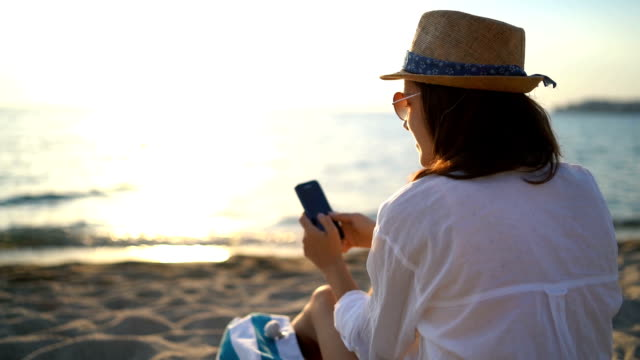 using phone at the beach - text messaging stock videos & royalty-free footage