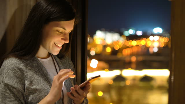 using phone by the window - street light stock videos & royalty-free footage