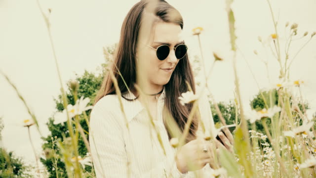 Using phone, cool girl in a meadow.