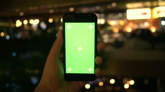 använda telefon: digital display på natten - över axel perspektiv bildbanksvideor och videomaterial från bakom kulisserna