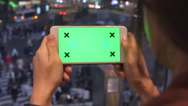 mittels telefon greenscreen, shibuya menge menschen hintergrund - halten stock-videos und b-roll-filmmaterial