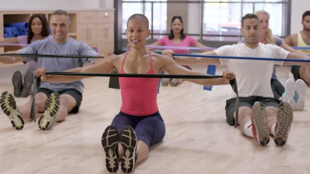 vídeos de stock, filmes e b-roll de usando faixas de resistência em uma aula de fitness - boa postura