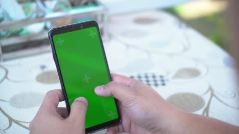 använda smart phone grön skärm - oskriven bildbanksvideor och videomaterial från bakom kulisserna
