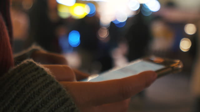 using smart phone in christmas market. - online messaging stock videos and b-roll footage