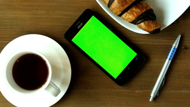 Using smart phone on green screen with desert, pen and coffee on work wood table