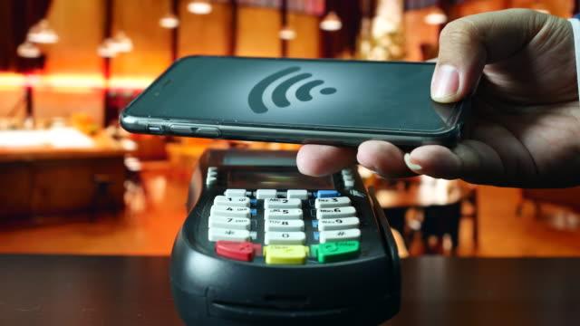 vídeos de stock, filmes e b-roll de usando o telefone inteligente pagar no restaurante, pagamento sem contacto - pagamento móvel