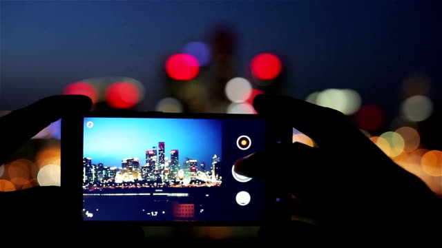 using smart phone take photo in city night - photography themes stock videos & royalty-free footage